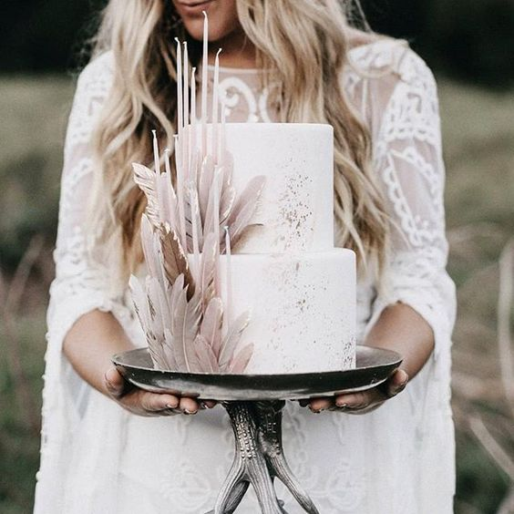 a white wedding cake with silver leaf and blush sugar feathers and thin and tall candles in blush