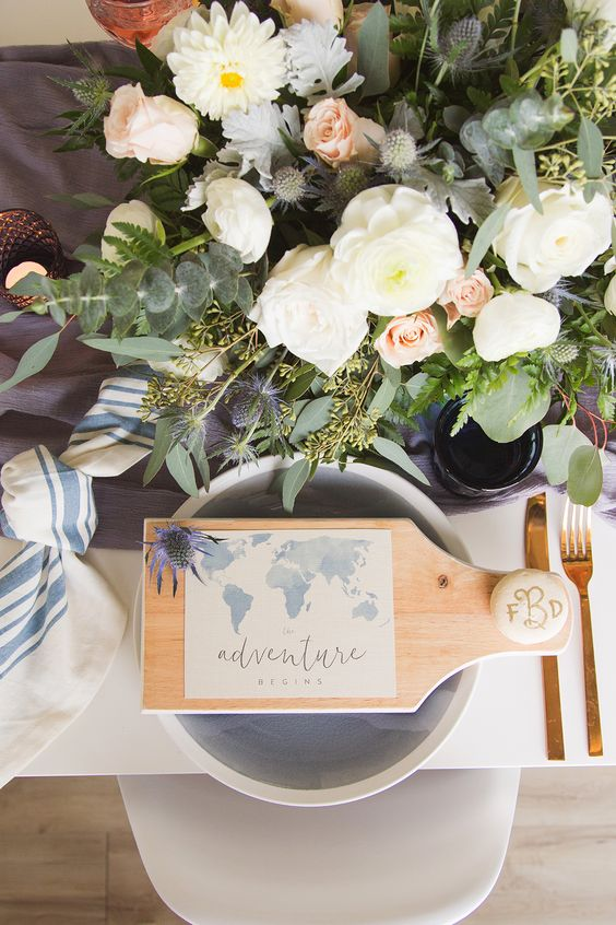 a wooden board with a map and a pebble with a monogram is a cool idea to mark each place setting