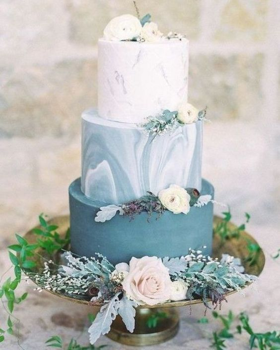 an adorable wedding cake with a plain blue, blue marble and white marble tier, white blooms and pale leaves