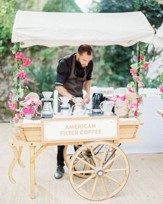 an elegant coffee bar decorated with pink blooms and greenery and styled as a vintage cart looks very chic