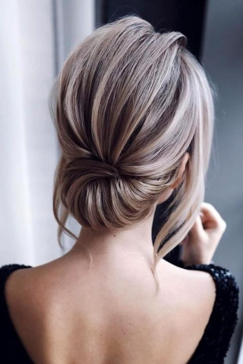 an elegant low updo with a dimensional bump and locks down is a stylish modern hairstyle