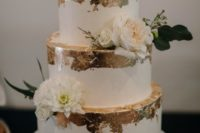 an elegant white wedding cake with gold leaf, white blooms and leaves and some twigs looks chic