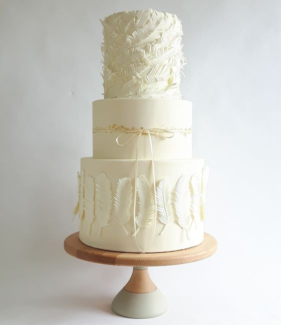 an ethereal white wedding cake with feather tiers and a plain one with gold leaf plus a ribbon bow