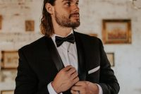 an exquisite black tux look with a man bun and some waves down that make it a bit more relaxed and casual