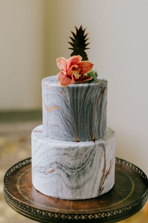 an exquisite wedding cake with grey marble tiers, copper leaf and a bold tropical bloom and a pineapple topper is cool