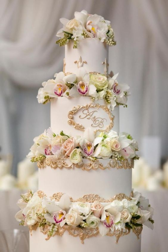 an exquisite white wedding cake with gold patterns and pastel and white blooms is a great idea for a formal wedding