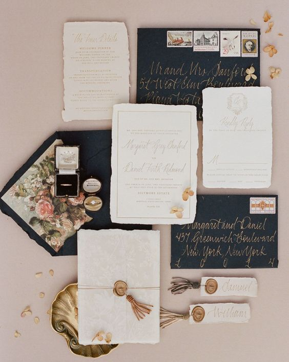 an eye-catchy wedding stationery suite with navy envelopes and gold calligraphy, with beautiful floral lining and a raw edge