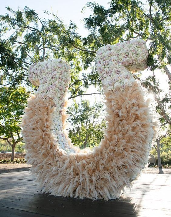 an oversized lucky horseshoe wedding altar made of pampas grass and fresh florals looks really wow