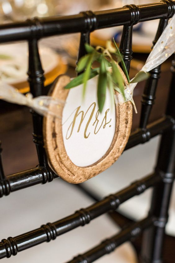 mark your wedding chairs with gold horseshoes and signs plus greenery instead of usual signs