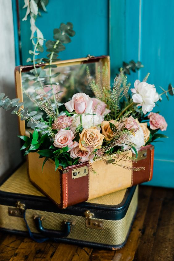 travel themed wedding decor of a stack of suitcases, greenery and pastel blooms is a cool and fun idea