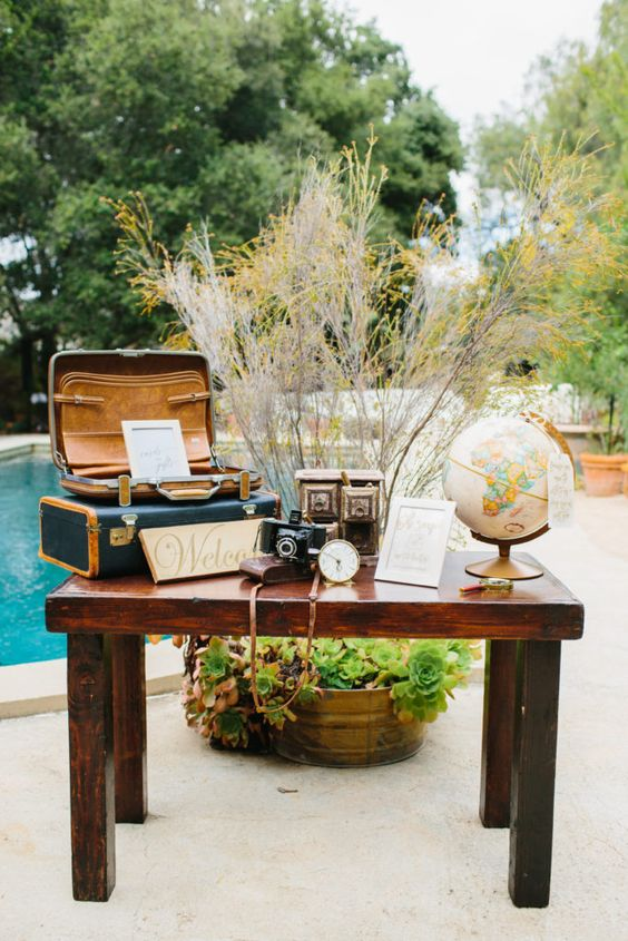 travel-themed wedding decor - suitcases, a globe, vintage cameras and greenery and branches behind the table