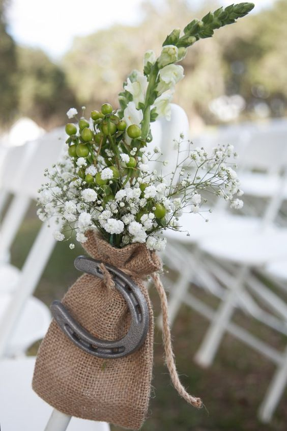 wedding aisle chair decor done with baby's breath, berries, a burlap sack with a horseshoe