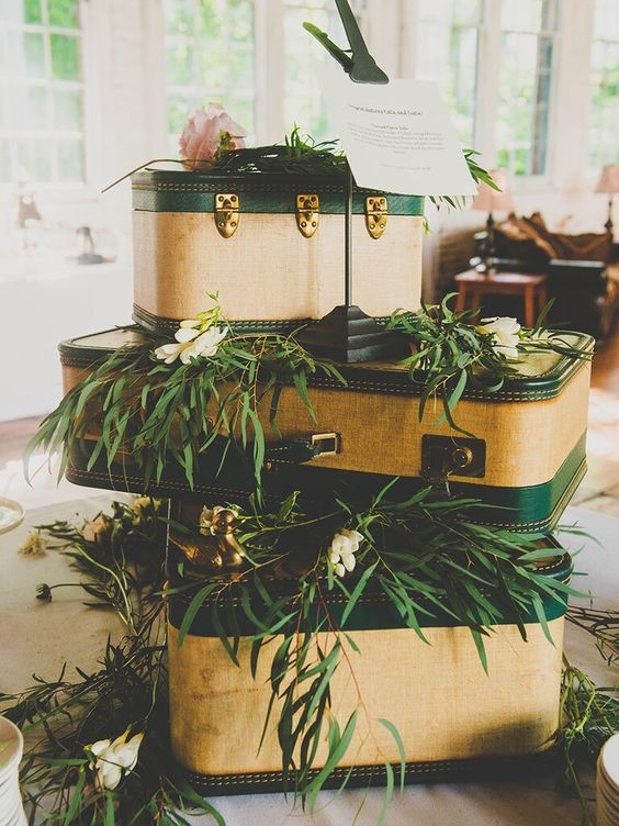 wedding decor done with vintage suitcases stacked on each other, greenery, white and pink blooms and a tag on top