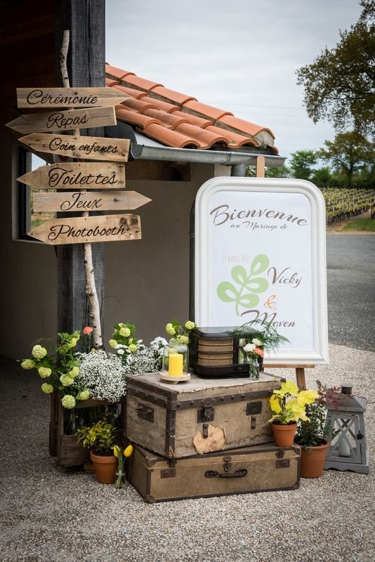wedding decor of vintage suitcases, bright yellow blooms, a sign, candle lanterns and a sign with wooden elements