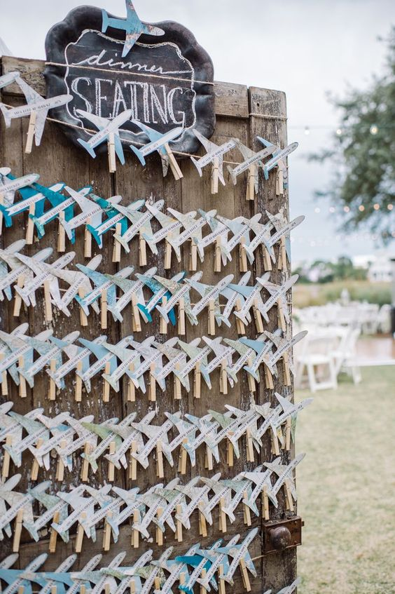 wedding escort cards styled as little planes of map paper can double as fun wedding favors