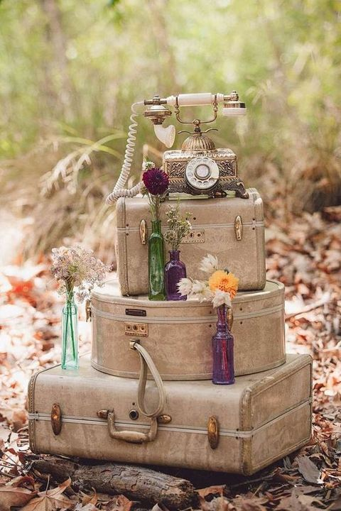 whimsy vintage travel wedding decor of stacked suitcases, bright blooms and a vintage telephone