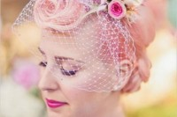 a retro updo with pink hair, birdcage veil with white and pink blooms for a rockabilly bridal look