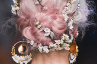 a fantastic spring bridal hairstyle with pink hair – a braided updo accessorized with blooming branches and with statement earrings