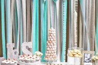 a dessert table with a silver, cream and tiffany blue ribbon backdrop to create an ambience