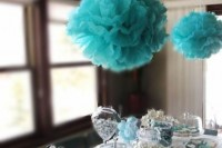 a dessert table with sweets in white and tiffany blue and with tiffany blue paper clouds over the table