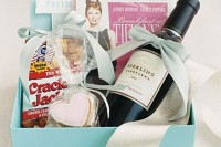 welcome or gift boxes in tiffany blue with a wine bottle, snacks, a film and a photo album
