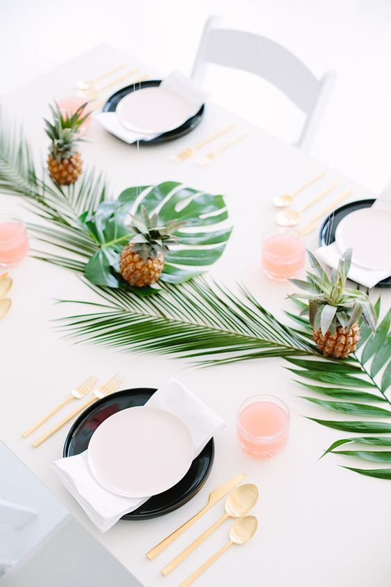 a bright tropical tablescape with a leaf table runner, pineapples, gold cutlery and black chargers