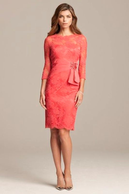 a coral pink lace over knee dress with long sleeves and a high neckline is a bright and chic idea