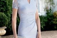 a light blue sheath knee dress with lace sleeves and a deep neckline plus a shiny white bag