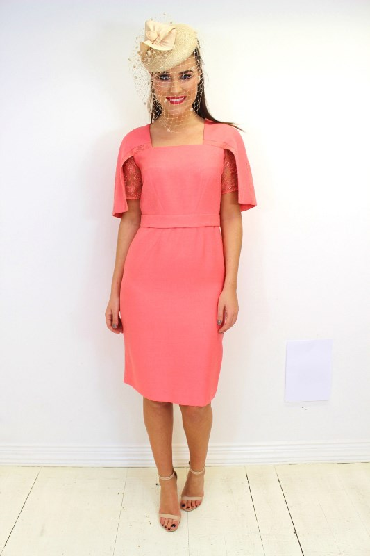a bright pink sheath knee dress with short lace sleeves, a trendy square neckline and a whimsy hat with a birdcage veil