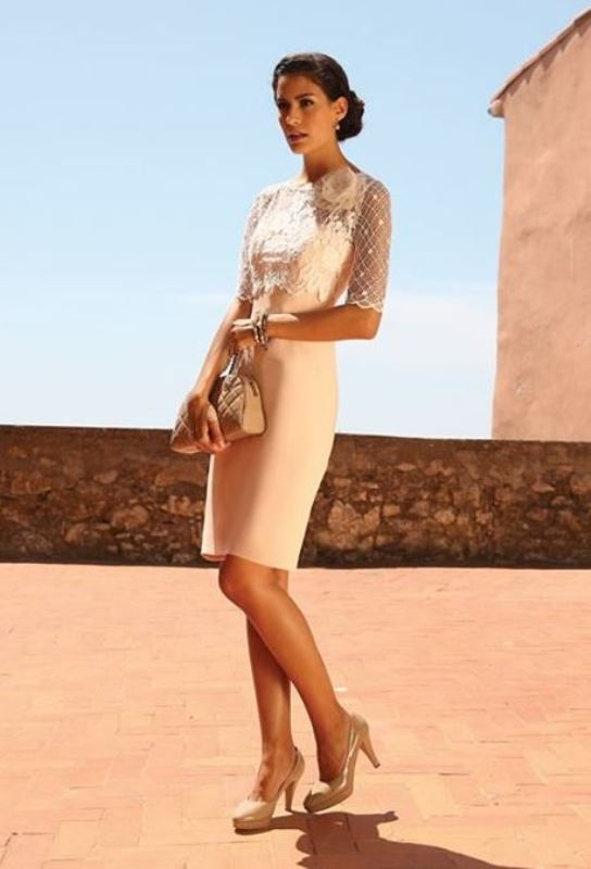 a neutral sheath dress with a lace bodice and short sleeves, nude shoes and a nude mini bag