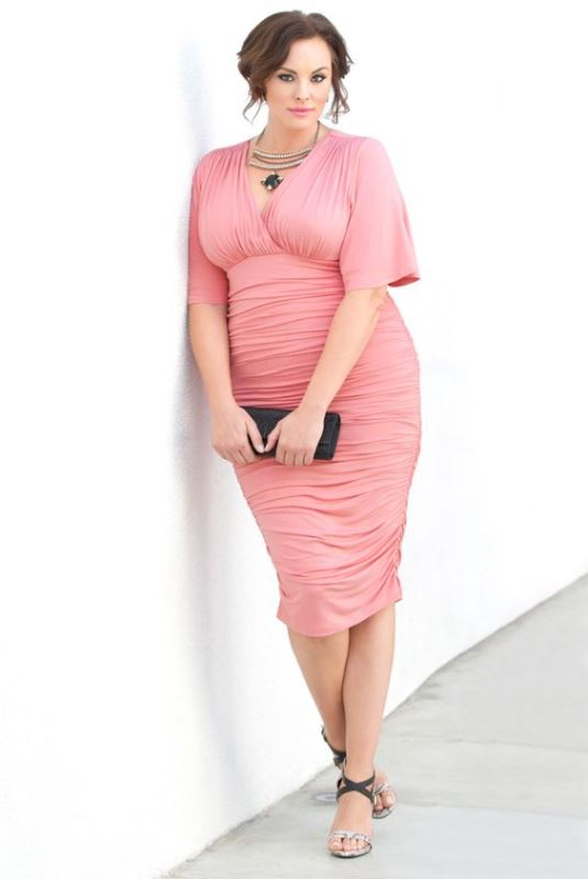 a chic fitting pink draped midi dress with short sleeves, heels and a statement necklace to highlight your curves