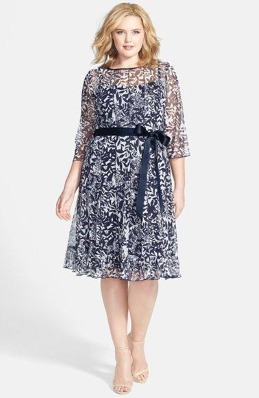 a navy and white botanical print knee dress with short sleeves and a sash to accent the waist