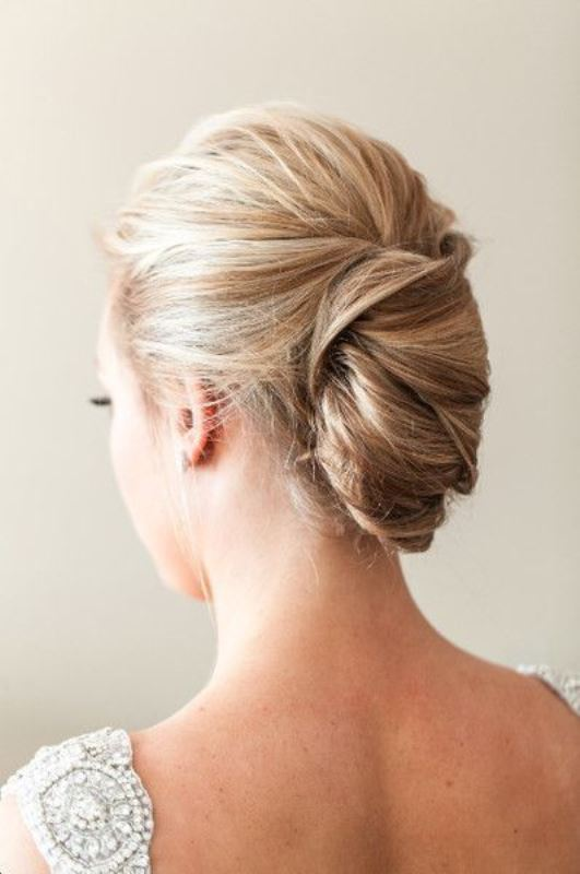 a tight French twist updo with a volume on top on balayage hair for a chic and stylish look