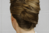 a very formal French twist updo with a large volume on top and ombre hair that makes it more spectacular