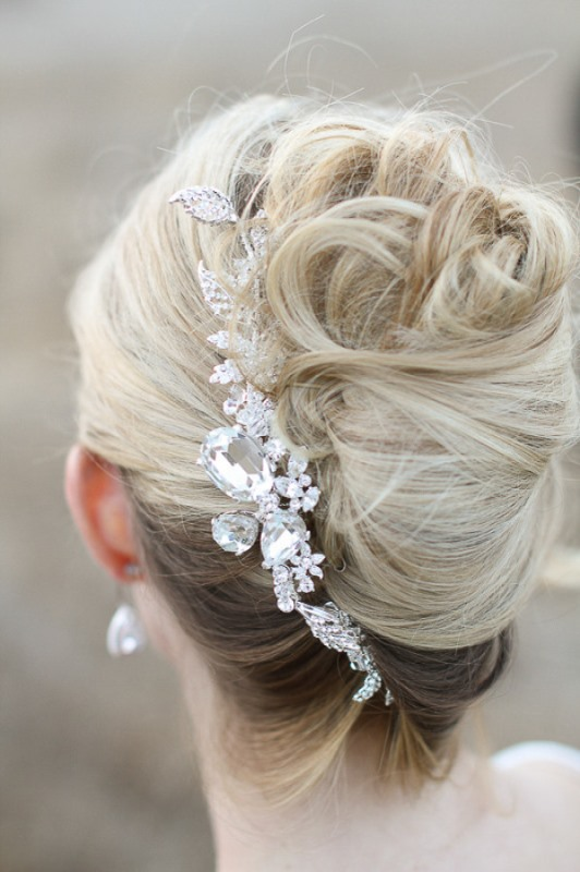 a super messy and chic French twist updo with messy waves and a large rhinestone hairpiece