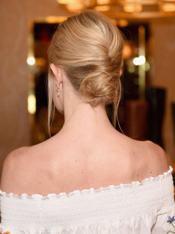 a low French twisted updo with a volume on top and locks down is a stylish idea for a effortlessly chic bride