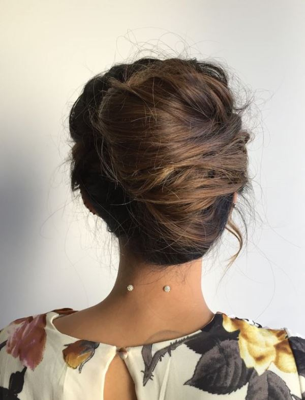 a messy French twist updo on long hair, with much texture and dimension and some locks down