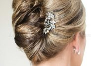 a very formal and refined French twist updo with a volume on top and a rhinestone brooch for an accent