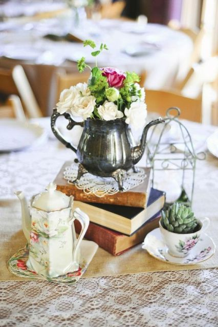 a catchy vintage centerpiece of a stack of books, a silver teapot with blooms, a potted succulent, a cage and a coffee pot