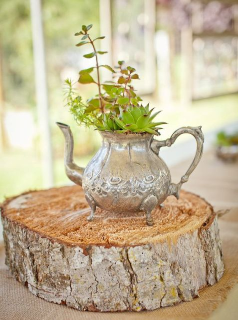 a cute centerpiece of a wood slice, a vintage silver teapot as a vase for succulents and greenery