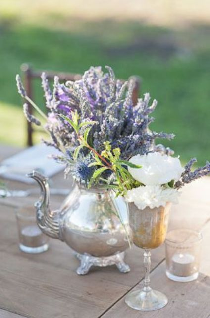 a gorgeous wedding centerpiece of a silver teapot with lavender and thistles, a white blooms in a silver glass