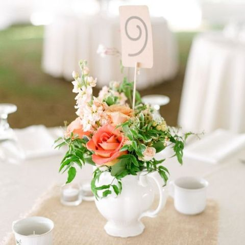 a white teapot with coral and blush blooms plus greenery and a table number on a stand