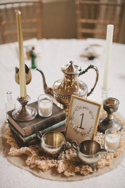 a vintage wedding centerpiece made of a doily, candles, vintage silver teaware and a teapot plus a candle