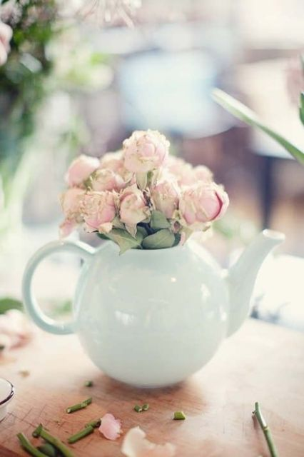 an off-white teapot used as a vase for pink peonies is a cool and relaxed centerpiece idea
