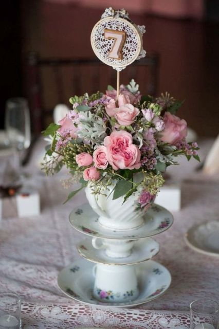 floral vintage teacups and a teapot on top with usual and pale greenery, pink blooms and and a topped with macrame and a table number