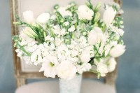 white tulips, smaller white blooms, greenery and peonies in a bouquet with a white wrap