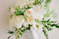 a textural white bridal bouquet with blooms and greenery of various kinds plus a neutral wrap