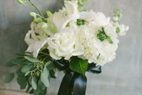 a textural white wedding bouquet with greenery, a dark green bow and much dimension