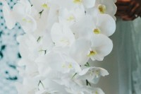 a stylish all-white orchid wedding bouquet