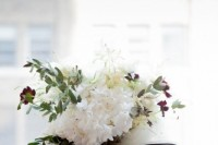 a white wedding bouquet spruced up with greenery and touches of burgundy blooms plus a striped bow